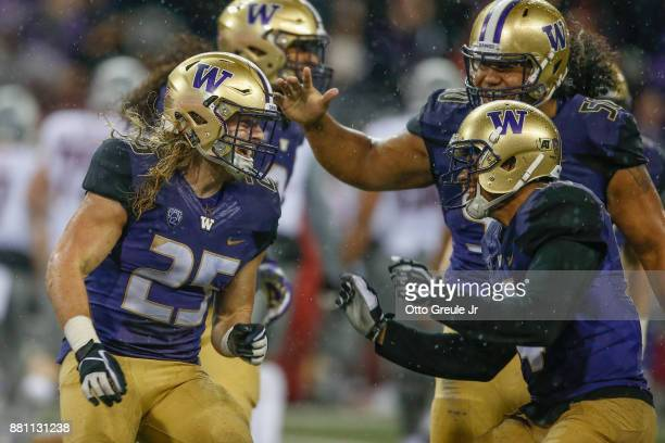 Linebacker Ben BurrKirven of the Washington Huskies is congratulated by teammates after making an interception against the Washington State Cougars...