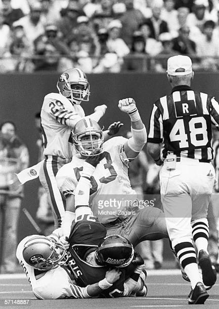 Linebacker Bill Romanowski and safety Tom Holmoe of the San Francisco 49ers tackle running back Joe Morris of the New York Giants at Giants Stadium...