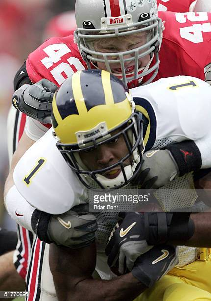 Linebacker Bobby Carpenter of the Ohio State Buckeyes tackles wide receiver Braylon Edwards of the Michigan Wolverines during the first half on...