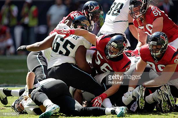 Linebacker Brian Cushing of the Houston Texans dives into a pile to make a tackle on quarterback Blaine Gabbert of the Jacksonville Jaguars at...