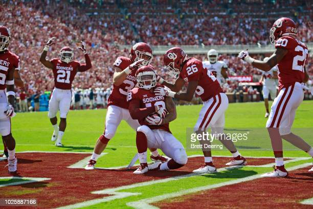 Linebacker Bryan Mead and defensive back Caleb Murphy congratulate linebacker Curtis Bolton of the Oklahoma Sooners who recovered a blocked punt to...