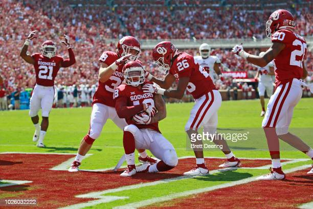 Linebacker Bryan Mead and defensive back Caleb Murphy congratulate linebacker Curtis Bolton of the Oklahoma Sooners after scoring on a blocked punt...