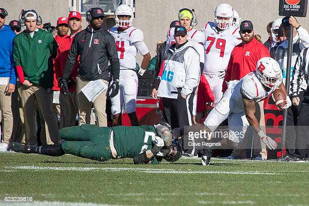 Linebacker Chris Frey of the Michigan State Spartans grabs the leg and tackles running back Robert Martin of the Rutgers Scarlet Knights during a...
