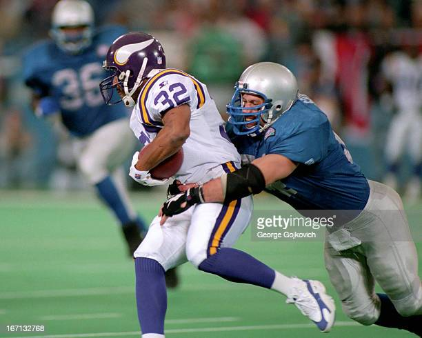 Linebacker Chris Spielman of the Detroit Lions tackles running back Amp Lee of the Minnesota Vikings during a game at the Pontiac Silverdome on...