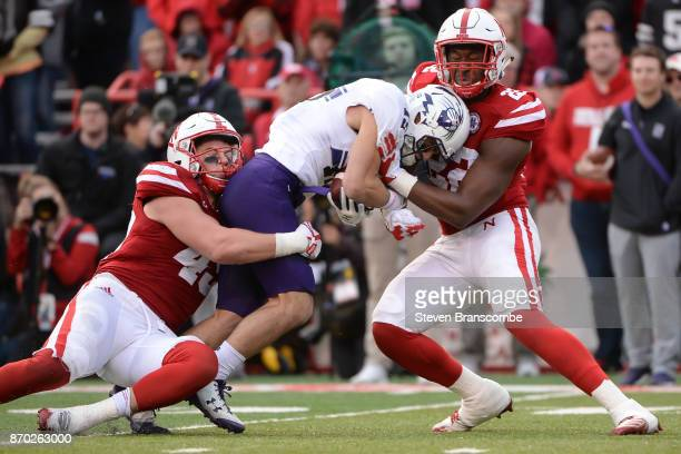 Linebacker Chris Weber of the Nebraska Cornhuskers and linebacker Alex Davis combine to tackle wide receiver Macan Wilson of the Northwestern...