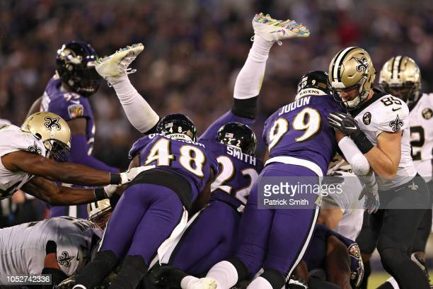 Linebacker C.J. Mosley of the Baltimore Ravens us upended as quarterback Drew Brees of the New Orleans Saints dives with the ball to convert on a...