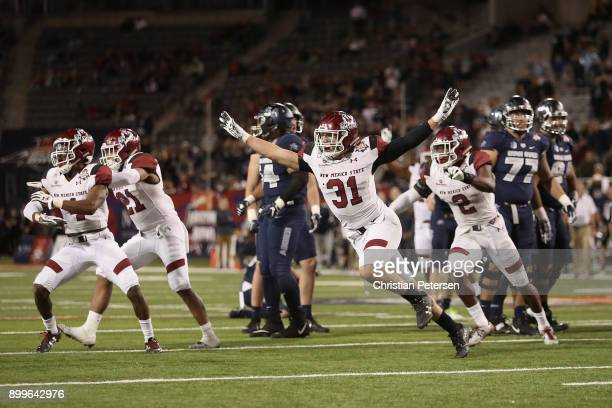 Linebacker Dalton Herrington of the New Mexico State Aggies celebrates with teamamtes after the Utah State Aggies missed a field goal in overtime of...