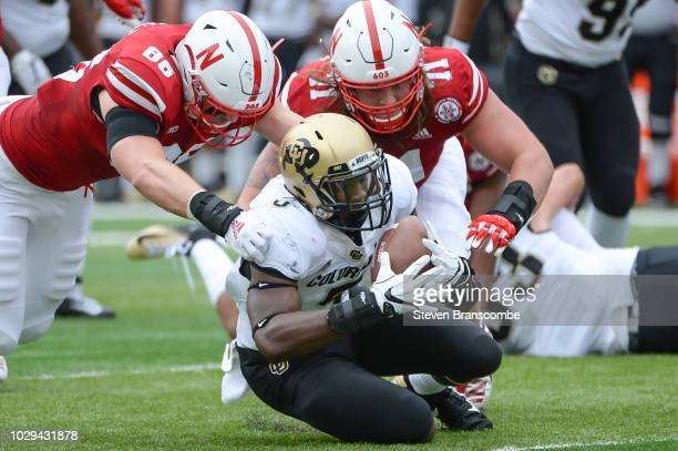 Linebacker Davion Taylor of the Colorado Buffaloes recovers a first quarter fumble against the Nebraska Cornhuskers at Memorial Stadium on September...