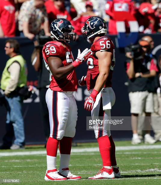 Linebacker DeMeco Ryans of the Houston Texans talks with teammate Brian Cushing between plays at Reliant Stadium on October 30 2011 in Houston Texas...