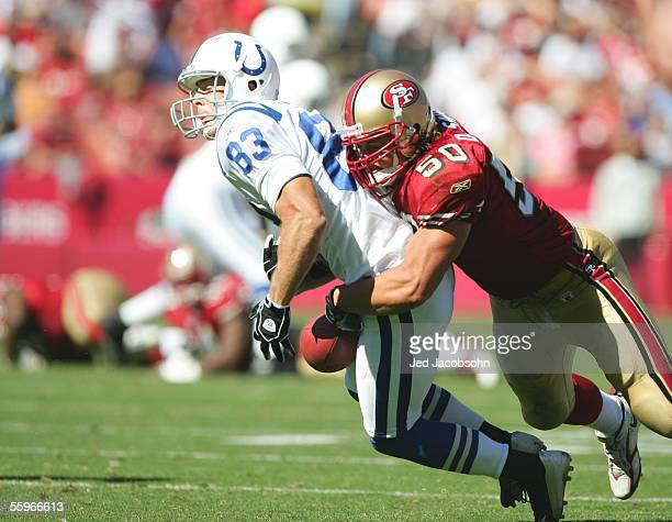 Linebacker Derek Smith of the San Francisco 49ers hits wide receiver Brandon Stokley of the Indianapolis Colts and causes him to drop the ball at...