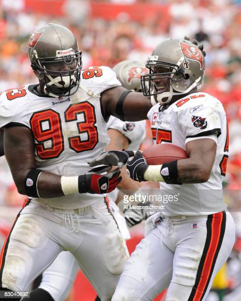 Linebacker Derrick Brooks and defensive end Kevin Carter of the Tampa Bay Buccaneers celebrate an interception against the Green Bay Packers at...
