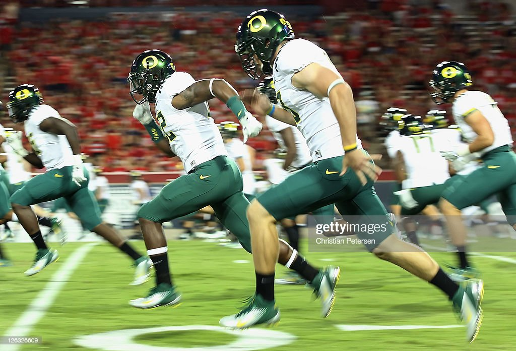 Linebacker Derrick Malone #22 (second from left) of the Oregon Ducks warms up with teammates before the college football game against the Arizona Wildcats at Arizona Stadium on September 24, 2011 in Tucson, Arizona. The Ducks defeated the Wildcats 56-31.