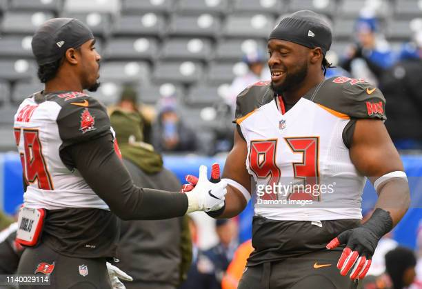 Linebacker Devante Bond and defensive tackle Gerald McCoy of the Tampa Bay Buccaneers shake hands prior to a game against the New York Giants on...