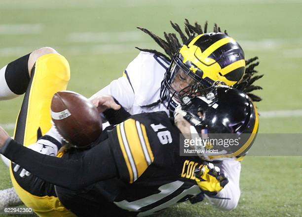 Linebacker Devin Bush of the Michigan Wolverines makes a tackle during the first quarter on punter Ron Coluzzi of the Iowa Hawkeyes on November 12...