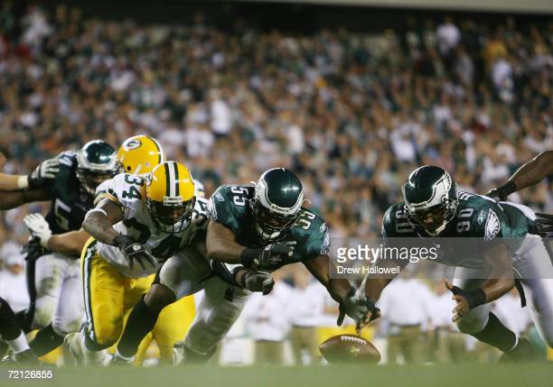 Linebacker Dhani Jones and defensive end Darren Howard of the Philadelphia Eagles dive and recover a fumble by running back Vernand Morency of the on...