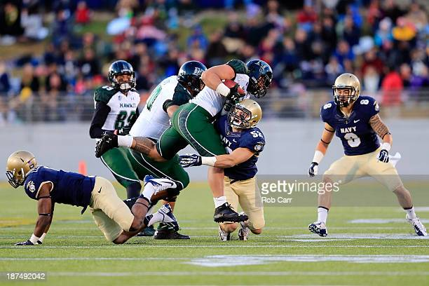 Linebacker DJ Sargenti of the Navy Midshipmen tackles running back Joey Iosefa of the Hawaii Warriors during the second quarter at NavyMarine Corps...