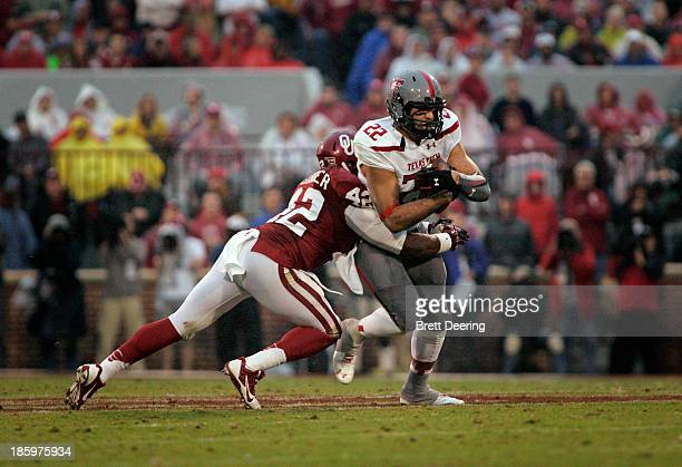 Linebacker Dominique Alexander of the Oklahoma Sooners tries to take down tight end Jace Amaro of the Texas Tech Red Raiders October 26 2013 at...