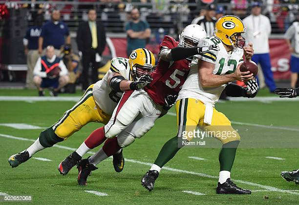 Linebacker Dwight Freeney of the Arizona Cardinals of the Arizona Cardinals forces a fumble on quarterback Aaron Rodgers of the Green Bay Packers at...