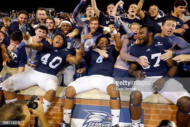 Linebacker Edwin Jackson, quarterback Kevin Ellison and linebacker Antwione Williams of the Georgia Southern Eagles celebrate with the student...