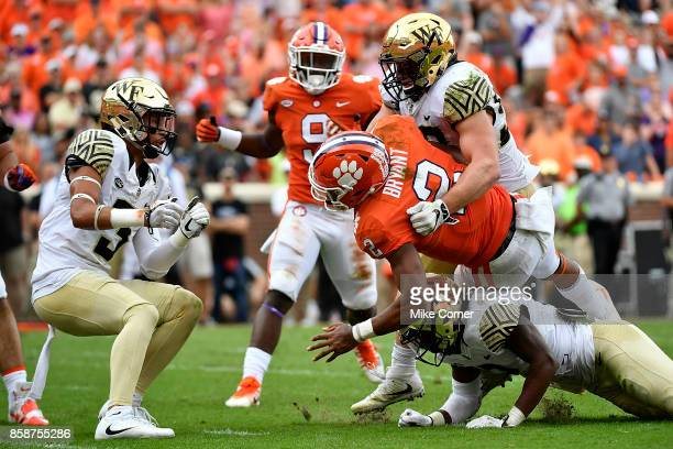 Linebacker Grant Dawson and defensive back Cameron Glenn of the Wake Forest Demon Deacons tackle quarterback Kelly Bryant of the Clemson Tigers...