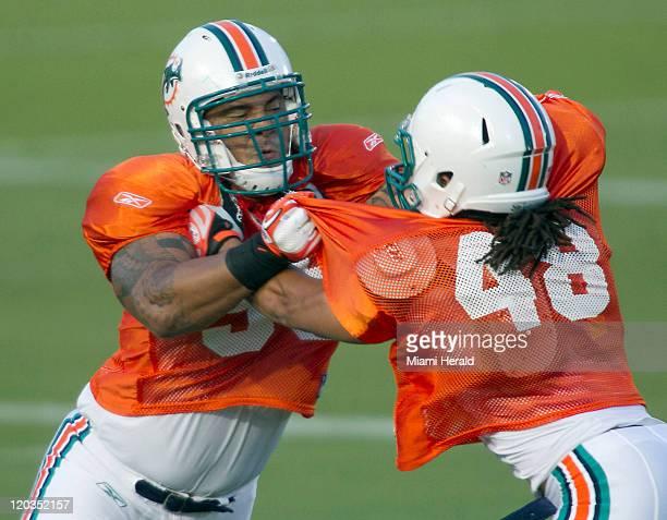 Linebacker Ikaika Alana-Francis, left, tangles with linebacker Jason Trusnik during the Miami Dolphins' training camp on Thursday, August 4 at the...