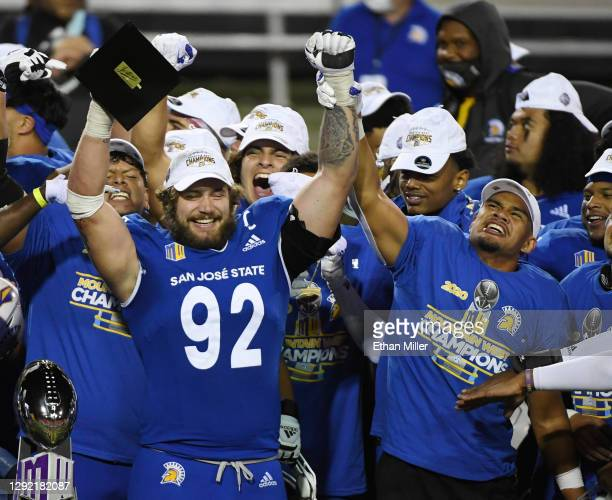 Linebacker Isa'ako Togia of the San Jose State Spartans holds up the arm of defensive lineman Cade Hall as he lifts up the the Mountain West...