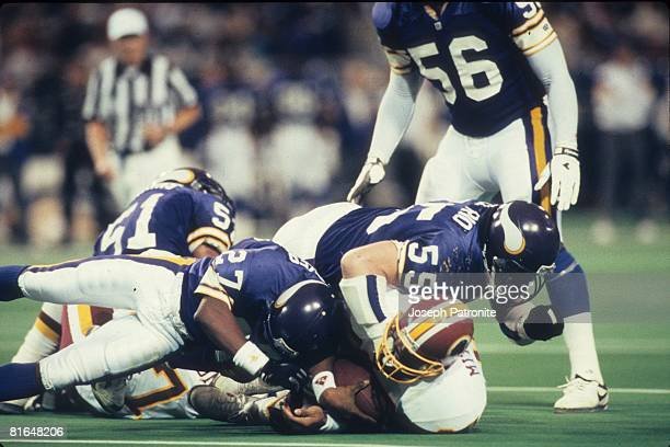 Linebacker Jack Del Rio and cornerback Anthony Parker of the Minnesota Vikings bring down tight end Ron Middleton of the Washington Redskins in the...