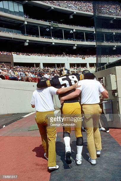 Linebacker Jack Lambert of the Pittsburgh Steelers is helped to the lockerroom after injuring his foot during a game against the Kansas City Chiefs...