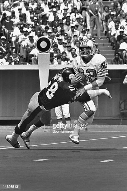Linebacker Jack Lambert of the Pittsburgh Steelers tackles wide receiver Mike Renfro of the Houston OIlers on September 7 at Three Rivers Stadium in...