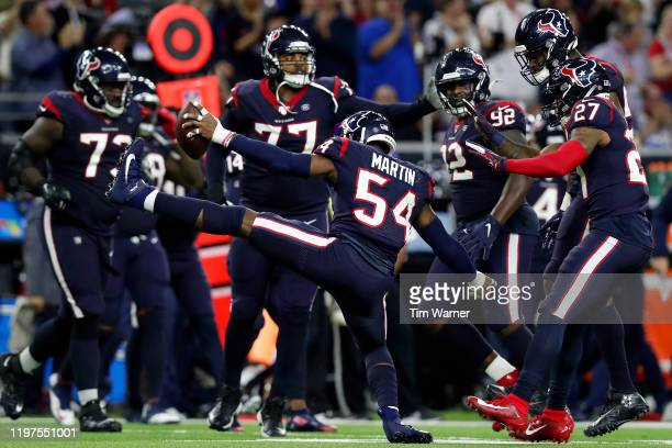 Linebacker Jake Martin of the Houston Texans celebrates with teammates after recovering a fumble in the fourth quarter of the AFC Wild Card Playoff...
