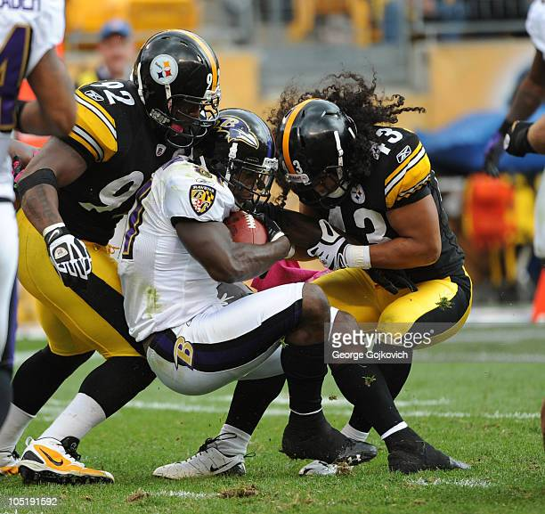 Linebacker James Harrison and safety Troy Polamalu of the Pittsburgh Steelers tackle wide receiver Anquan Boldin of the Baltimore Ravens during a...
