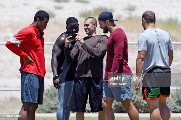 Linebacker Javin White , cornerback D.J. Killings safety Erik Harris and fullback Alec Ingold of the Las Vegas Raiders look at images on a cell phone...
