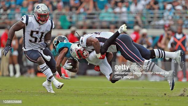 Linebacker Ja'Whaun Bentley of the New England Patriots looks on as linebacker Dont'a Hightower of the New England Patriots tackles wide receiver...