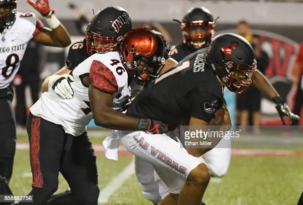 Linebacker Jay Henderson of the San Diego State Aztecs sacks quarterback Armani Rogers of the UNLV Rebels during their game at Sam Boyd Stadium on...