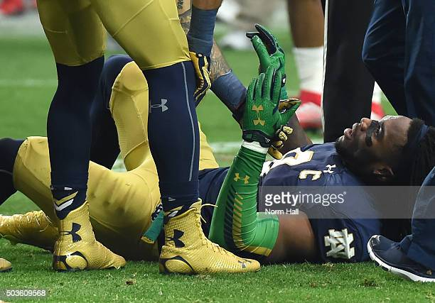 Linebacker Jaylon Smith of the Notre Dame Fighting Irish holds the hand of a teammate after suffering an injury during the first quarter of the...