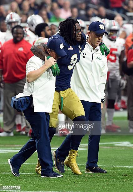 Linebacker Jaylon Smith of the Notre Dame Fighting Irish is helped off the field after suffering an injury during the first quarter of the BattleFrog...