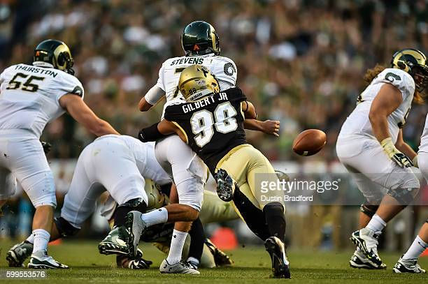 Linebacker Jimmie Gilbert of the Colorado Buffaloes hits quarterback Nick Stevens of the Colorado State Rams and forces a fumble at Sports Authority...