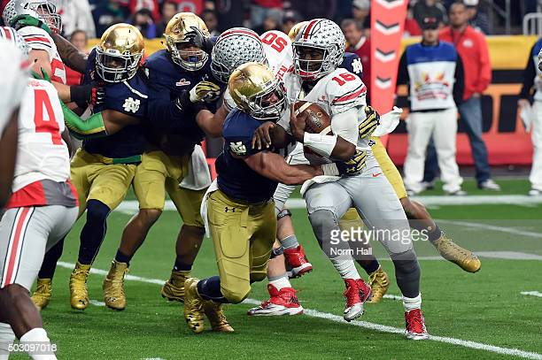Linebacker Joe Schmidt of the Notre Dame Fighting Irish hits quarterback JT Barrett of the Ohio State Buckeyes during the first quarter of the...