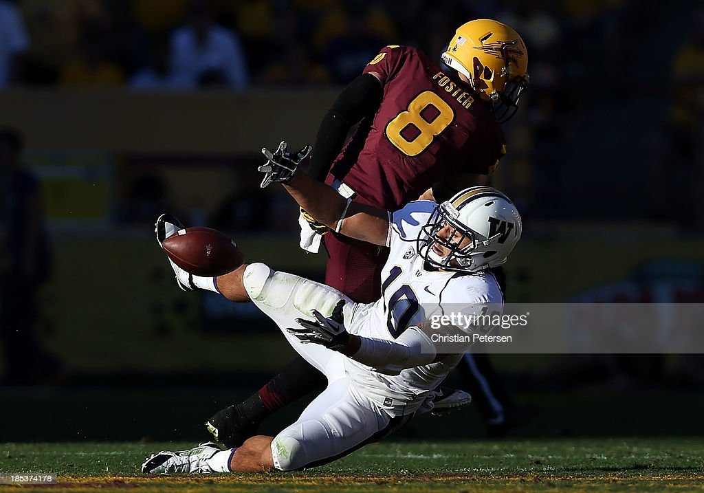 Linebacker John Timu #10 of the Washington Huskies attempts an interception ahead of running back D.J. Foster #8 of the Arizona State Sun Devils during the college football game at Sun Devil Stadium on October 19, 2013 in Tempe, Arizona. The Sun Devils defeated the Huskies 53-24.