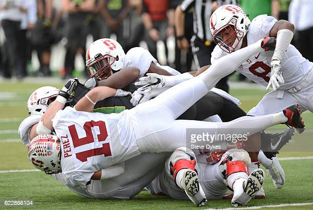Linebacker Jordan Perez of the Stanford Cardina and safety Justin Reid join in to help gang tackle running back Royce Freeman of the Oregon Ducks...