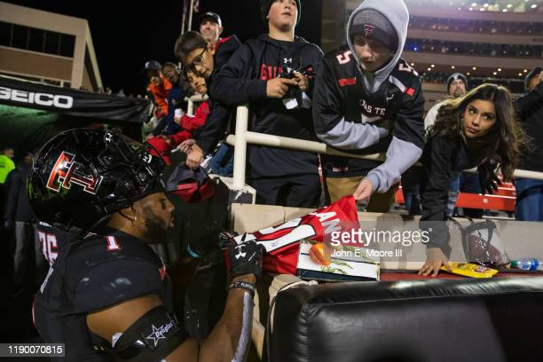 Linebacker Jordyn Brooks of the Texas Tech Red Raiders signs autographs for fans after the college football game against the Kansas State Wildcats on...