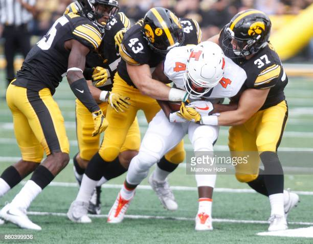 Linebacker Josey Jewell and safety Brandon Snyder of the Iowa Hawkeyes wrap up wide receiver Ricky Smalling of the Illinois Fighting Illini in the...
