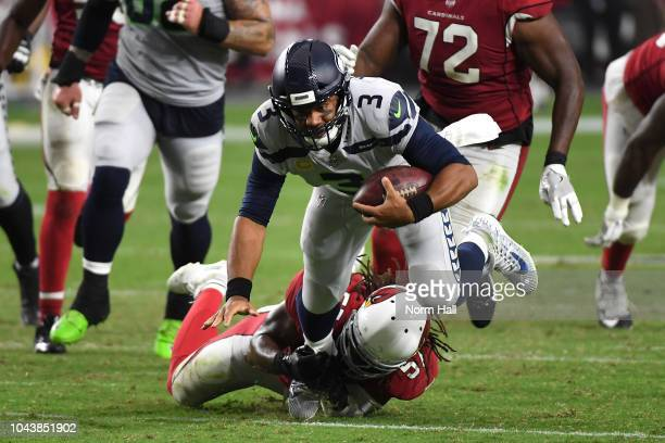 Linebacker Josh Bynes of the Arizona Cardinals tackles quarterback Russell Wilson of the Seattle Seahawks during the third quarter at State Farm...