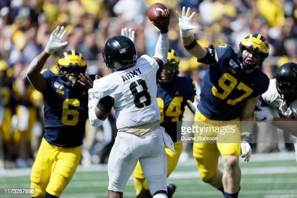 Linebacker Josh Uche and defensive lineman Aidan Hutchinson of the Michigan Wolverines defend against a pass by quarterback Kelvin Hopkins Jr #8 of...