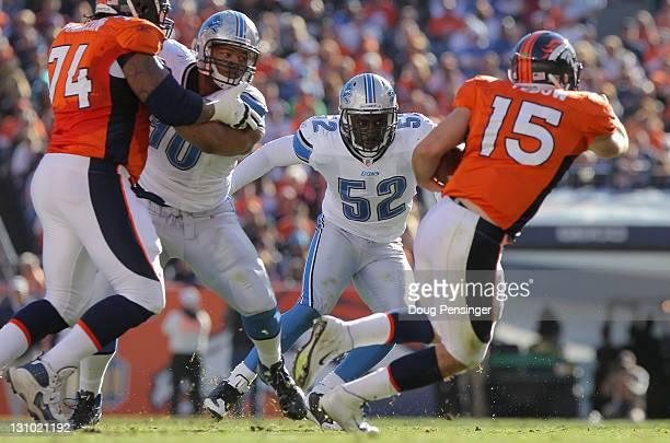 Linebacker Justin Durant of the Detroit Lions tries to contain quaterback Tim Tebow of the Denver Broncos as offensive lineman Orlando Franklin of...