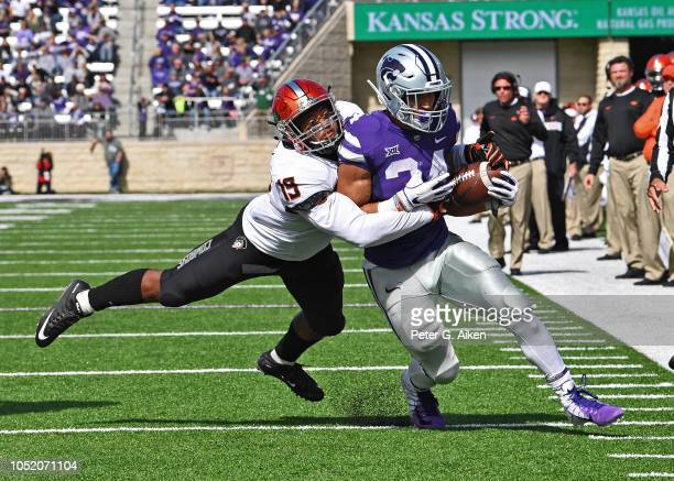Linebacker Justin Phillips of the Oklahoma State Cowboys tackles running back Alex Barnes of the Kansas State Wildcats from behind during the second...