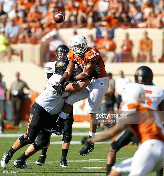 Linebacker Keenan Robinson of the Texas Longhorns is pushed out by offensive lineman Levy Adcock of the Oklahoma State Cowboys as a Brandon Weeden...