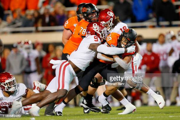 Linebacker Kenneth Murray and linebacker Caleb Kelly of the Oklahoma Sooners keep running back Chuba Hubbard of the Oklahoma State Cowboys contained...