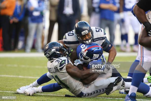 Linebacker KJ Wright and Safety Kam Chancellor of the Seattle Seahawks make a stop against the New York Giants during their game at MetLife Stadium...