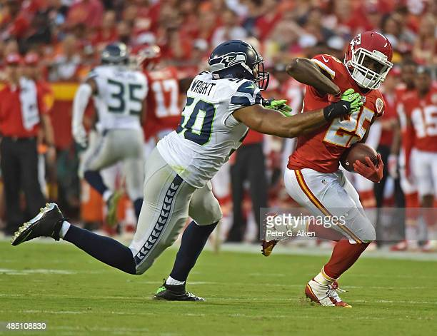 Linebacker KJ Wright of the Seattle Seahawks tackles running back Jamaal Charles of the Kansas City Chiefs during the first half of a preseason game...